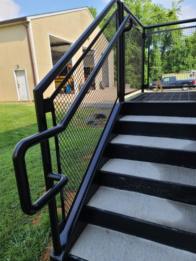 Exterior stair_cement tread pans_bar graded landing_exterior railing schedule 40 pipe with mesh insert