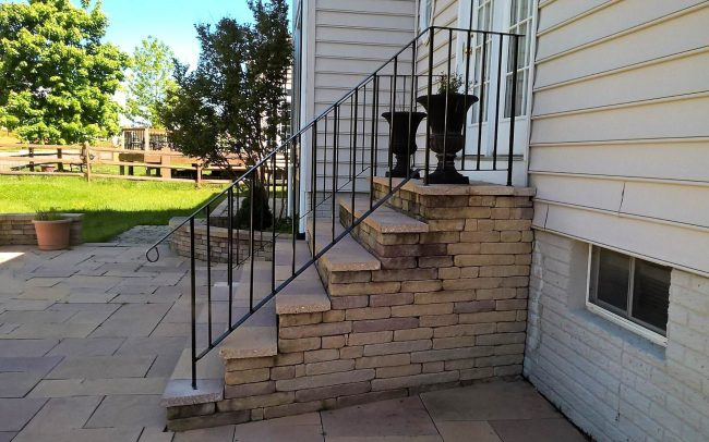 Exterior wrought iron rail_solid post_flat bar handrail_half inch square balusters_cement anchors and base plate_powder coated black