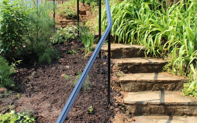 Exterior wrought iron rail_solid posts_starting post cement anchor remaining cemented in ground black powder coating Vineyard