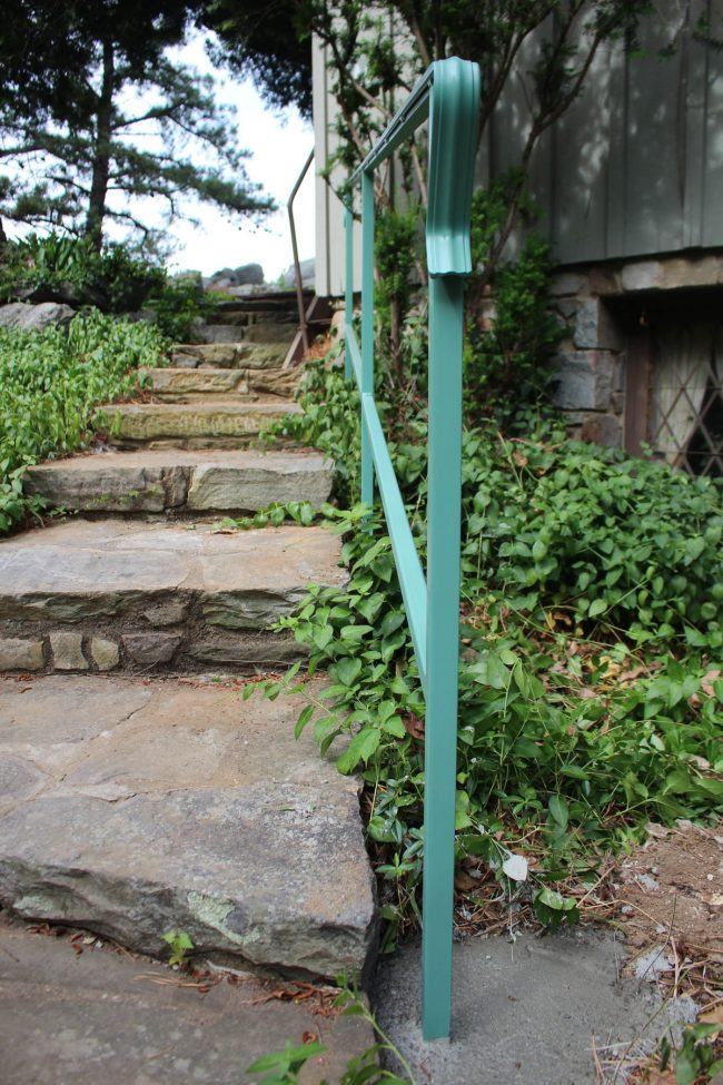 Exterior wrought iron railing with solid posts_cemented into ground_painted to match existing rails