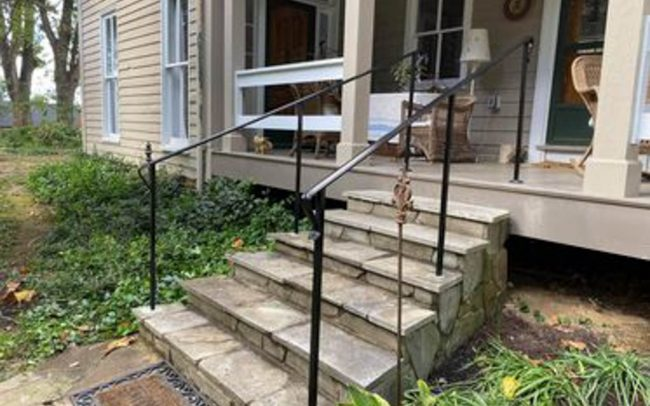 exterior wrought iron rail_solid post_core drilled_epoxy into flagstone_painted black_top post base plate and lag bolt mounted